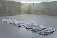 very strong instalation by Maurizio Cattelan, seem like sheet covered bodies, are actualy made of marble. (def art)