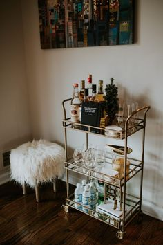 world market bar cart decor, gold bar cart, bar cart target, faux sheepskin stool, faux fur stool, what to put on a bar car, bar cart ideas, holiday hosting, how to host a holiday party, gold champagne glasses, gold rimmed wine glasses, agate coasters // grace wainwright a southern drawl