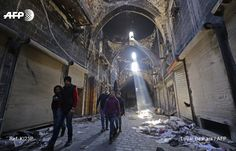 Syrian children walk down a damaged street in the old city of Aleppo on January 22, 2017, a month after government forces retook the city from rebel fighters. LOUAI BESHARA / AFP