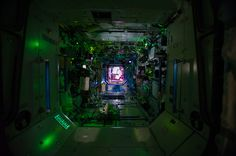 This view in the International Space Station, photographed by an Expedition 40 crew member, shows how it looks inside the space station while the crew is asleep. The dots near the hatch point to a Soyuz spacecraft docked to the station in case the crew was to encounter an emergency. This view is looking into the Destiny Laboratory from Node 1 (Unity) with Node 2 (Harmony) in the background.