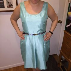 "Pleated Turquoise Taffeta Dress with Belt Size 12 Pleated Turquoise Taffeta Dress including Belt Size 12. Only worn once. Photos show dress with and without the flash. It is slightly shiny in person, somewhere in between the two photos. I'm 5'4"", and it comes to below my knee. Perfect for spring bridal showers and weddings! Dresses"