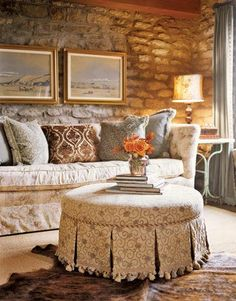 Sophisticated fabrics add subtle structure to the limestone-walled room while still maintaining the natural tones of the room. Love the upholstered stool.