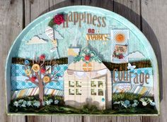 "I love mixed media pieces with a lot of character – and there is so much that I love about this ""happiness""  piece from Mitra. I love the wood background with Mod Podge and sparkle . . . the kite . . . the layers behind the house . . . the tree with buttons.... Read More »"
