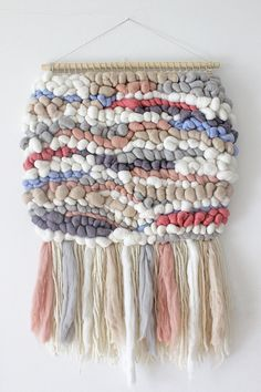 "This fluffy and colorful woven wall hanging is a true eye catcher and is guaranteed to brighten any room it hangs in. The colors and textures of this wall hanging gives the piece a dreamy look and is perfect addition to baby nursery! Made with merino wool roving and wool yarn. Colours are true but please be aware that there may be differences between my monitor and yours. Hung on a 50 cm (20"") wooden dowel, this weaving hangs 85 cm (33"") long from the dowel to end of fringe (longest…"