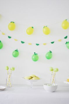 It was only a matter of time before we turned the fruity balloon straw concept into other party projects! Turns out they make for perfect mini fruit garlands! Looking at these now I wish I had done more balloons so the look was a little fuller but I still like these little lemons and limes! Materials Water balloons // Balloon pump // String // Tape // Scissors // Green cardstock // Leaf templates 1. Use the balloon pump to blow up your yellow and green water balloons. 2. Tie the string ar...