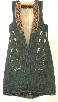 "Embroidered Vest - A long vest of boiled and pressed white wool covered with a dense wool embroidery of dark green and blue with a gold thread embroidered velvet ribbon along the neckline. Worn on festive occasions in the Attica region of Greece.   Greece, 19th century, wool, velvet is slightly worn, otherwise very good condition, 11"" (across the shoulders) x 34"""