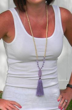 Tassels! You need this necklace in your life. Super fun and on trend. Grab several and stack 'em together! Natural wood beaded necklace featuring wooden beads, purple beads, a stone pendant and a fun