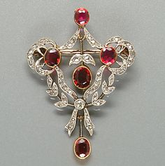 A belle époque ruby and diamond brooch/pendant, circa 1905  The stylised tied ribbon and foliate design set with five graduated oval-cut rubies, the whole set throughout with rose-cut diamonds, to a rose-cut diamond-set suspensory hoop and a fine belcher-link chain, length of pendant 4.0cm