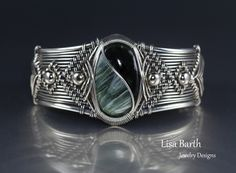 I wove this bracelet in a way to enhance the stone's natural two tone coloration.  Wire weaving done in sterling wire -  Lisa Barth