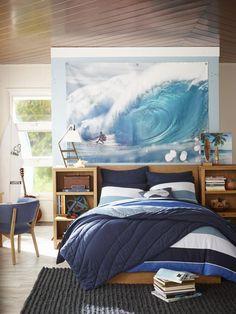 Poster mit Wellenreiter an der Wand hinter dem Bett