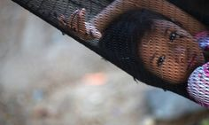Soe, the eight-year-old daughter of a fisherman from Myanmar, rests in a hammock outside her family home in Ban Nam Khem