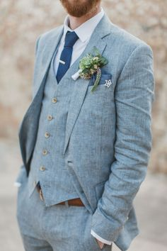 Groom in a three piece gray suit and slate blue accessories.