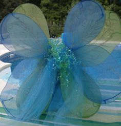 Use 2 dollar store butterfly wings, blue netting and some sparkling Easter grass for butterfly table decorations.