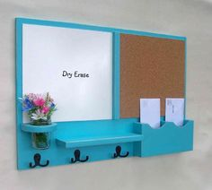 Blue dry erase/cork board with mail organizer, mason jar holder (could be used as a plant or pencil holder) little shelf, and hooks.