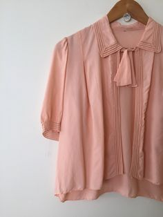 The most lovely little 1930s bolero jacket made from peachy pink rayon.  The jacket features puff sleeves that end at the elbow, a pointed collar and fine cutwork stitching around the sleeve cuffs and collar. The jacket fastens at the neck with ties.  M E A S U R E M E N T S  Size: small to medium  Bust: 36 / 92cm Sleeve: 12 / 30cm Length: 20 / 51cm  E R A: 1930s  F A B R I C: rayon  B R A N D: no tags  C O N D I T I O N: the jacket has a few small marks and some separation of a small part…