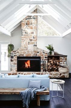 A pale blue sofa sits in front of the basalt fireplace, a stand-out feature of the Soul of Gerringong farmhouse. The stonework was completed by Broughton Stonemasonry and the fire box is from Jetmaster. Behind the sofa is a wooden bench from St Barts, while the side table is from Globe West. | Photography: Mark Roper | Styling: Jessica Hanson