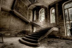 Abandoned structure with arched windows and staircase