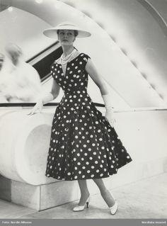 1963. Original från Maggie Rouff. Vitt hatt, original Balmain. Modell vid rulltrapporna på Nordiska Kompaniet. Klädd i prickig klänning. Foto: Nordin Nilsson