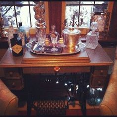 Antique sewing machine converted into a liquor cabinet. Add some wheels and could become a home bar cart.