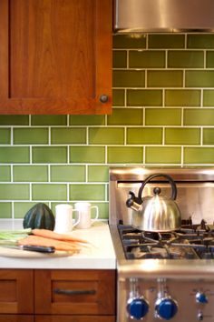Stainless steel appliances, green tiles, and rich wood cabinets give this kitchen a chic urban organic vibe.