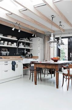 Love the black wall, shelving, light fittings are gorgeous and the skylight is great, it needs a recycled timber floor though.