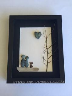 Our personalized couples gifts and customized pebble art work is made with a variety of treasures from the beautiful beaches of West Coast Canada. Showcased in an 8 X 10 X 1 inch black shadow box frame is a stone couple, that are catching a quiet moment together with their beloved dog. Truly a whimsical, peaceful scene. The beach stones, some lovely twig, and driftwood give the piece a nautical feel. A unique heart shaped rock makes this piece extra special. The treasures are carefully…
