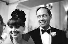 The actress Audrey Hepburn photographed with her husband Mel Ferrer (actor, dialogue coach and film director) at the Teatro Victoria Eugenia, located on Avenida República Argentina, in San Sebastián (Spain), during their arrival forthe award ceremony of the XII San Sebastián International Film Festival (in Spanish: Festival de San Sebastián), on June 14, 1964.Audrey was wearing:Evening ensemble: Givenchy (of organdie in a shade of bright orange, stole and sleeveless gown, with a jewel…