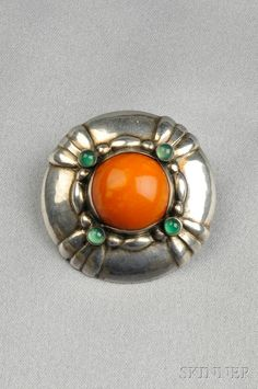 Georg Jensen, Silver, Amber, and Chrysoprase Brooch,  designed by Georg Jensen, set with a large amber cabochon and four chrysoprase cabochons, no. 50, dia. 1 1/2 in., signed with background of dots stamped in oval surrounding Georg Jensen and 830 in circle of dots.