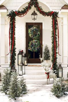 This gorgeous outdoor holiday display features rope garland, red ribbon, lanterns, and a few reindeer for an unexpected surprise!