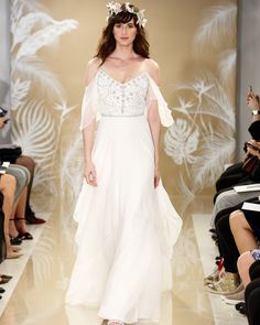 """The temperature might be changing from cold to colder in New York City, but at THEIA'sFall 2017 Bridal Fashion Weekshow, things were warming up. Creative Director Don O'Neill swept away runway attendeesinto somewhat of an island paradise with thedécor, and more importantly, the wedding dresses.Inspired by destination weddings, this season'sTHEIA bride """"longs for warm sand between her toes and bright lagoon blue waters to form the perfect contrast to her wh..."""