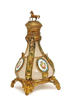 1850s Palais Royal perfume bottle, white opaline crystal, unusual gilt metal holder, alternating belt straps and porcelain floral medallions (two with lines), hinged cover, horse finial, inner stopper. 7 1/2 in.