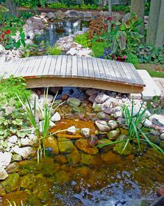 Small footbridge over backyard landscape waterfall and pond