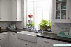 Love the big window, farm house sink, and cabinets displaying the white pitcher and ceramic strawberry baskets.