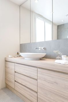Love this bright and airy bathroom with modern bathroom cabinet design. Light wood, simple cabinet profile, huge mirror, white vessel sink, wall mounted faucet.
