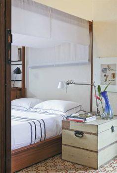 Quarto com cama de madeira cumaru (Mac) e dossel coberto de linho (Vitrine by Casa Fortaleza). Sobre o baú (Mac), luminária Tolomeo, da La Lampe, e quadro da Stile Doc.