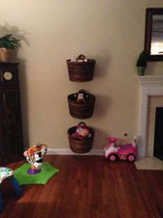Family Room - Toy Storage: What a creative and stylish way to keep little ones organized in an adult space!  Just a few preferred toys.  Hanging the baskets so that they are removable means your child can go choose an activity from a toy room allowing for changes as the child's interests change.  Command brand hooks mean basket heights can change as the child grows.