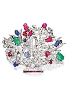 PLATINUM, DIAMOND AND COLORED STONE BROOCH The fanciful flower basket set with numerous variously-cut diamonds weighing approximately 6.90 carats, accented with carved and cabochon rubies, emeralds and sapphires, further accented by calibré-cut rubies, one diamond missing.