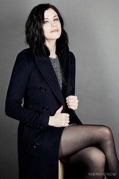 Jessica De Gouw wears a knit mini dress, navy blue coat, and tights