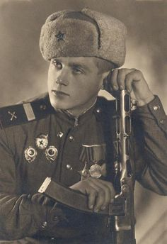 A formal portrait of a Russian soldier and a PPSh-41 Shpagin submachine gun fitted with the less common 32-round magazine