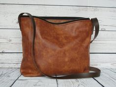 Tan leather shoulder bag: lightweight and versatile - perfect size for carrying your everyday things in style. Made with a vintage-look, upholstery-weight tan leather; practical and can be worn crossbody too. YKK metal zipper. Natural suede lining with triple stitched seams for strength at the base corners. Adjustable brown leather strap and antique-look rivets. Tobacco brown version also available (final photo.) ***Dimensions*** Width/Height/Depth: 34(top) x 26 x 8cm If you ha...