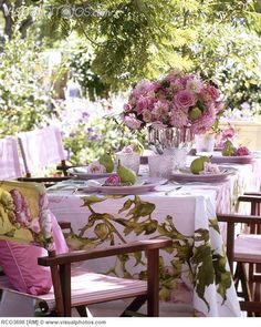 Table set with pink floral tablecloth for a summer afternoon tea party in a garden.