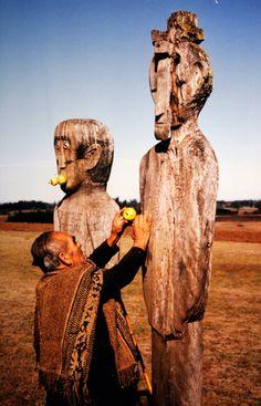 Hombre mapuche ofrendando manzanas a postes funerarios, chemamull. Fotografía de Martín Thomas. S/F. En: Archivo Fotográfico MCHAP.
