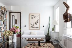 On the opposite end of the room, the second sofa is covered in a simple slipcover made from a vintage Italian linen remnant. A signed lithograph by Willem de Kooning, Love to Wakako, is the sole artwork on the wall.