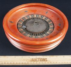 FUN VINTAGE MINIATURE ROULETTE WHEEL. THIS GAMBLING WHEEL IS PERFECT FOR THE HOME GAME TABLE, DUE TO ITS SIZE. CONSTRUCTED OF WOOD WITH BRASS ACCENTS. IT MEASURES 10 INCHES IN DIAMETER AND IS IN GOOD VINTAGE CONDITION.