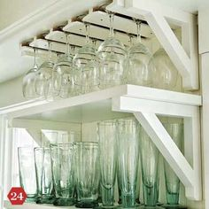 Use the underside of open shelves to store wine glasses and champagne flutes. Pick up the Oak Undercabinet Stemware Rack for about $30 at the Container Store
