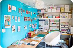 Craft studio in basement. I love the bright wall and hanging art.