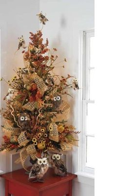 Great for a Fall display or a craft fair. A small evergreen tree filled in with straw and dried flowers and burlap ribbon and few owls. Fun easy to do with left over craft supplies.