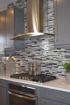This beautiful backsplash adds dimension to the kitchen and helps the vent stand out. Kitchen Cabinets Light Wood, Contemporary Kitchen Cabinets, Kitchen Cabinetry, Kitchen Tiles, Kitchen Room Design, Home Decor Kitchen, Kitchen Furniture, Kitchen Interior, Small Kitchen Redo