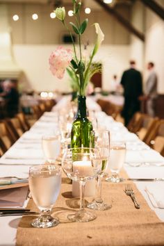 Bottles and jars with just a few stems of gorgeous flowers make a lovely and cost effective table arrangement.