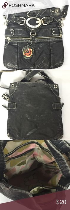 Distressed Leather Guess Bag Oversized and heavy weighted bag Out side has two zippered pockets, detachable mirror backed with a rose and a large G on the front of the bag  It has two shorter handles and a long strap Zippered top closure Inside has a zippered wall and open wall pockets Lining shows wear, it could be cleaned I am not sure if this is faux leather or real, it feels real. but cannot find the material tag. Bag Guess Bags Shoulder Bags